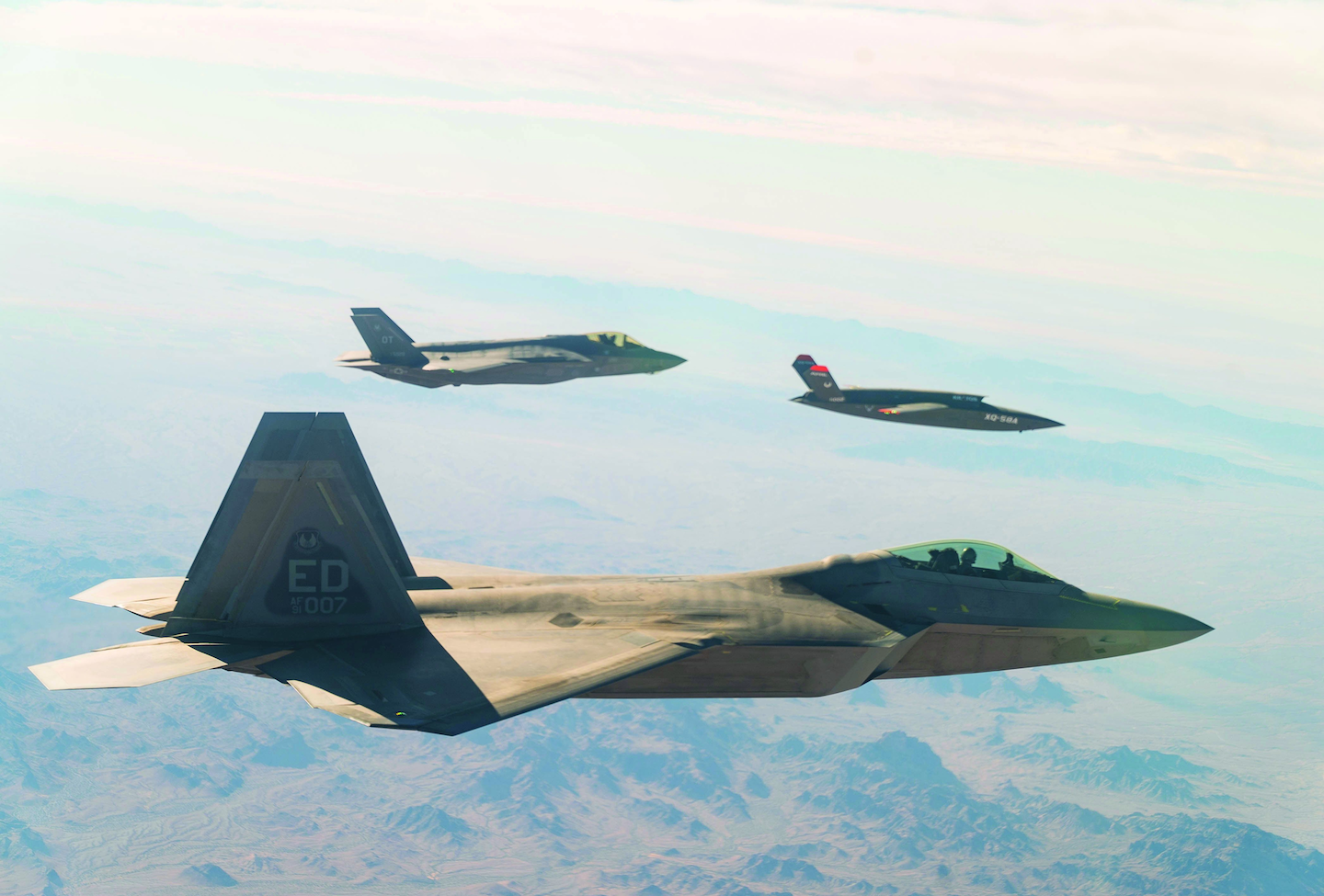 A U.S. Air Force F-22 Raptor and F-35A Lightning II manned combat aircraft fly in formation with the XQ-58A Valkyrie low-cost unmanned aerial vehicle over the U.S. Army Yuma Proving Ground testing range, Ariz.